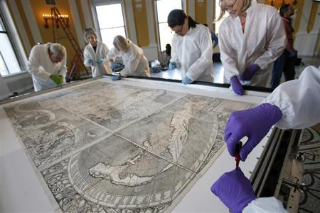 Conservators at the Library of Congress prepare a map for its encasement in Washington