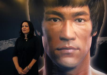Shannon Lee, daughter the late Kung Fu legend Bruce Lee, poses in front of a portrait of her father at the Hong Kong Heritage Museum