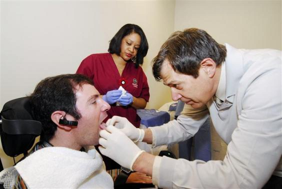 Paralyzed patient Jason Disanto's tongue is pierced in order for him to pilot a wheelchair using the Tongue Drive System at the Shepherd Center in Atlanta