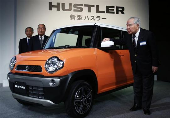 """Suzuki Motor Corp Chairman and CEO Suzuki, Executive Vice President Tamura, and Executive Vice President Honda pose next to its new boxy minicar """"HUSTLER"""" during its unveiling event in Tokyo"""